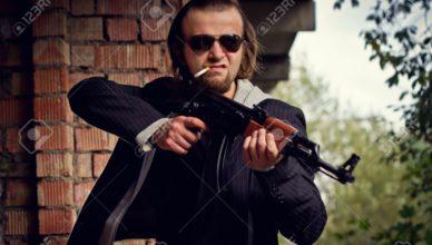 18242721-un-hombre-con-una-pistola-en-la-mano-y-un-cigarrillo-en-las-ruinas-de-la-casa-foto-de-archivo